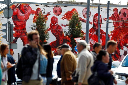 (AP Photo/Pavel Golovkin). People cross the road passing by the graffiti of the Marvel Universe fictional characters playing with soccer balls in the background in Moscow, Russia, Thursday, June 14, 2018, ahead of the opening match of the 2018 soccer W...