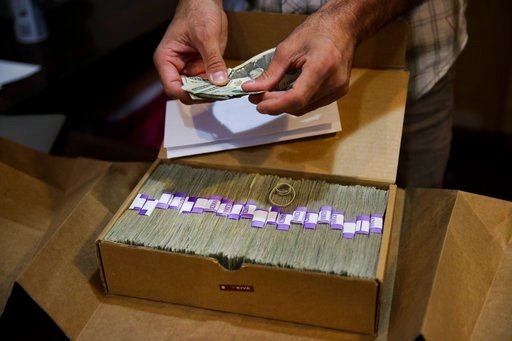 (AP Photo/Jae C. Hong, File). FILE - In this June 27, 2017 file photo, the proprietor of a medical marijuana dispensary prepares his monthly tax payment, over $40,000 in cash, at his Los Angeles store.  A proposal in Congress to ease the federal ban on...
