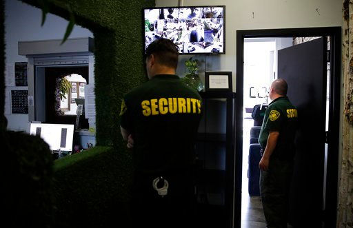 (AP Photo/Jae C. Hong, File). FILE - In this June 27, 2017 photo, two security guards stand watch at a medical marijuana dispensary in Los Angeles, a business conducted mostly in cash. The legal marijuana industry often finds the doors locked at banks,...