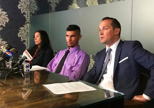 (AP Photo/Terry Tang). Jose Conde, center, listens to news media while seated between his mother, Rosa Conde, and attorney Bret Royle at Royle's office in Phoenix on Thursday, June 14, 2018. Recently released Mesa police videos show officers punching C...