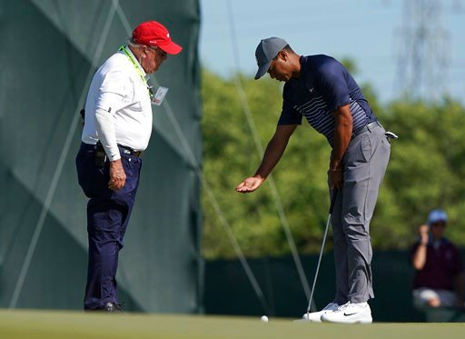 (AP Photo/Carolyn Kaster). Tiger Woods, right, talks with an official on the tenth green after the wind moved his ball after he addressed it during the first round of the U.S. Open Golf Championship, Thursday, June 14, 2018, in Southampton, N.Y.