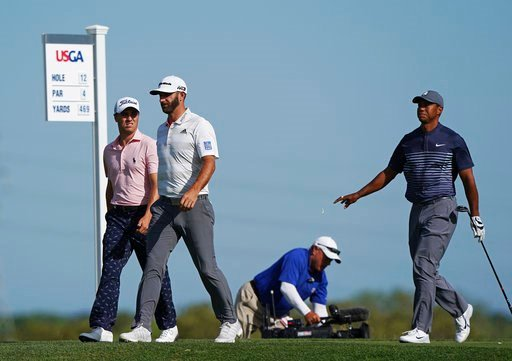 (AP Photo/Carolyn Kaster). From left, Justin Thomas, Dustin Johnson and Tiger Woods walk off the 12th tee during the first round of the U.S. Open Golf Championship, Thursday, June 14, 2018, in Southampton, N.Y.