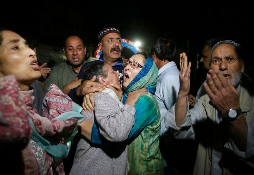(AP Photo/Mukhtar Khan). Relatives and friends of journalist Shujaat Bukhari cry inside a police control room in Srinagar, India, Thursday, June 14, 2018. Bukhari and his police bodyguard were shot and killed Thursday by assailants in Indian-controlled...