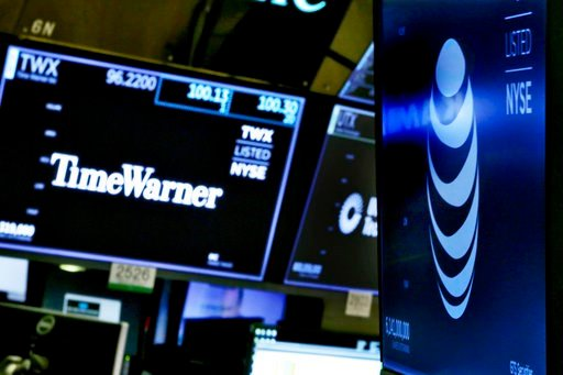 (AP Photo/Richard Drew, File). FILE - In this Wednesday, June 13, 2018, file photo, the logos for Time Warner and AT&T appear above alternate trading posts on the floor of the New York Stock Exchange. A federal judge has approved the $85 billion me...