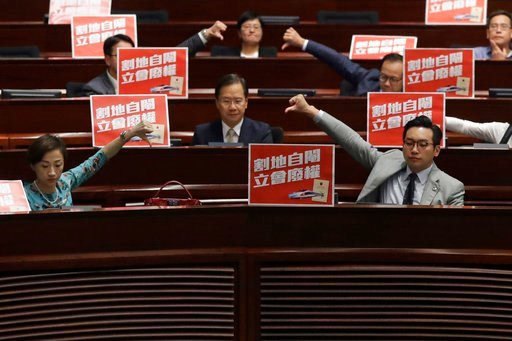 (AP Photo/Kin Cheung). Pro-democracy lawmakers react after a controversial bill had passed at legislative chamber In Hong Kong, Thursday, June 14, 2018. The Hong Kong Legislative Council had passed a controversial bill on Thursday on the co-location ch...