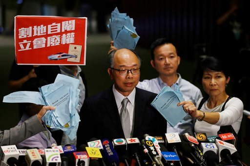 (AP Photo/Kin Cheung). Hong Kong Secretary for Transport and Housing Frank Chan Fan, center, speaks to the media surrounded by pro-democracy lawmakers after a controversial bill had passed, outside the legislative chamber In Hong Kong, Thursday, June 1...
