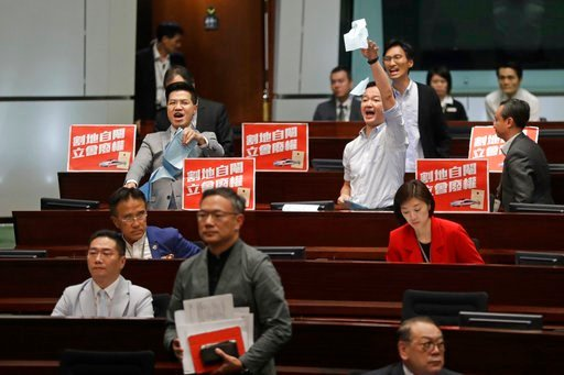 (AP Photo/Kin Cheung). Two pro-democracy lawmakers, at the back, shout and tear up the government documents after a controversial bill had passed at legislative chamber In Hong Kong, Thursday, June 14, 2018. The Hong Kong Legislative Council had passed...