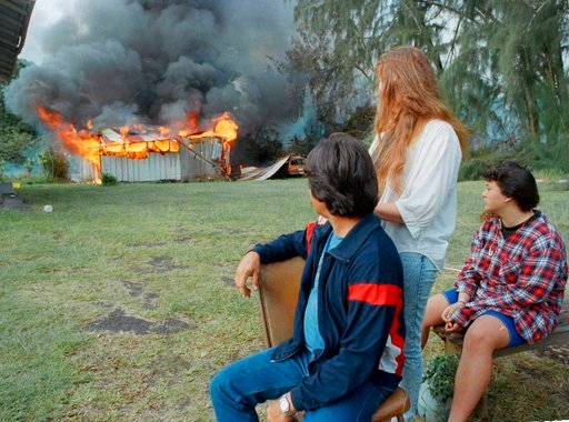 (AP Photo/Norman Shapiro, File). FILE - In this May 1, 1990 file photo, members of the Sweezey family watch as fire destroys their garage and threatens their house in Kalapana, Hawaii. Lava pouring out of Kilauea volcano burned down the whole town 28 y...