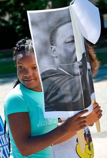 (Christopher Millette/Erie Times-News via AP). Friends Vaneya Collier, foreground, and Joslynn Cooley, background (obscured), both 11, of Erie, carry a poster depicting the Rev. Martin Luther King as they marched with about 160 people along West Sixth ...