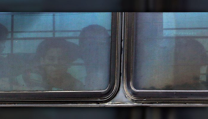 A boy stares out of a heavily tinted bus window leaving a U.S. Customs and Border Protection facility Tuesday in McAllen, TX. (AP Photo/Eric Gay)