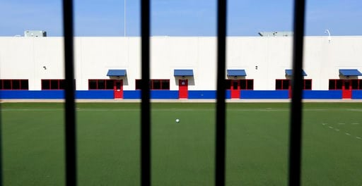 (AP Photo/Eric Gay, File). FILE - In this July 31, 2014, file photo, an artificial turf soccer field sits in the middle of the Karnes County Residential Center in Karnes City, Texas. The immigration detention facility has been retooled to house adults ...
