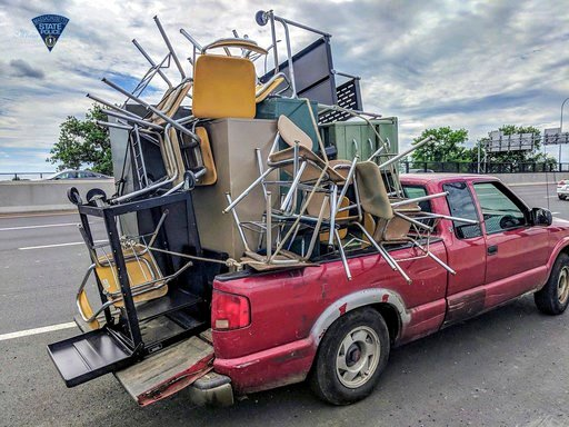 (Massachusetts State Police via AP). This June 20, 2018 photo released by the Massachusetts State Police shows an overloaded truck pulled over for uncovered cargo on Interstate 91 in Springfield, Mass. The same unnamed driver was pulled over in by poli...