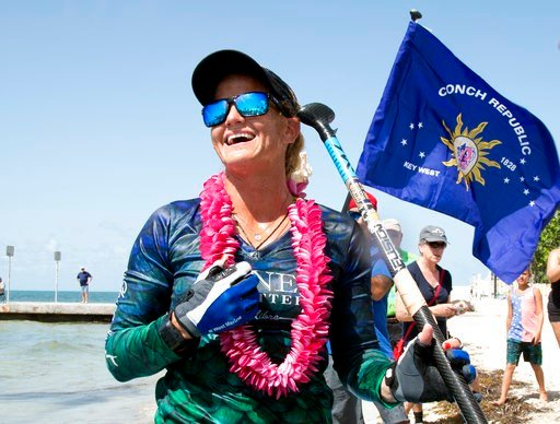(Carol Tedesco/Florida Keys News Bureau via AP). In this photo provided by the Florida Keys News Bureau, Victoria Burgess, beams with pride Wednesday, June 27, 2018, in Key West, Fla. after she standup paddleboarded from Cuba to the southernmost city i...