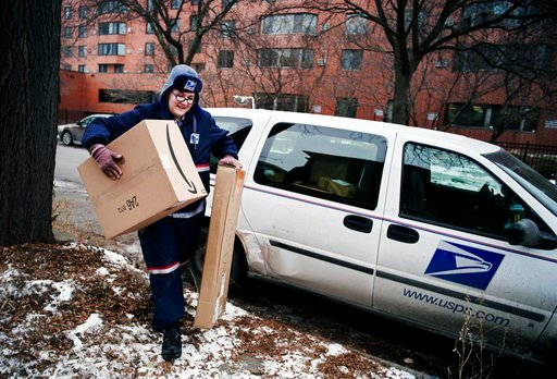 (Richard Tsong-Taatarii/Star Tribune via AP, File). FILE- In this Dec. 24, 2017, file photo, United States Postal Service worker Missie Kittok, who has been a letter carrier for 15 months, helps deliver some packages in time for Christmas in Minneapoli...