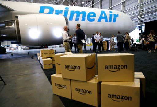 """(AP Photo/Ted S. Warren, File). FILE - In this Aug. 4, 2016 file photo, Amazon.com boxes are shown stacked near a Boeing 767 Amazon """"Prime Air"""" cargo plane on display in a Boeing hangar in Seattle. Amazon's Prime shipping program set the pace for shopp..."""