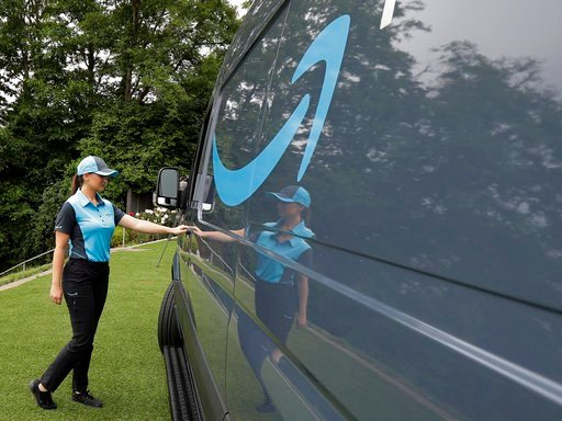 (AP Photo/Ted S. Warren, File). FILE- In this Wednesday, June 27, 2018, file photo, Parisa Sadrzadeh, a senior manager of logistics for Amazon.com, opens the door of an Amazon-branded delivery van at the request of a photographer in Seattle, following ...