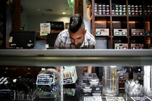 (AP Photo/Jae C. Hong, File). FILE - In this June 27, 2017, file photo, Jerred Kiloh, owner of the Higher Path medical marijuana dispensary, stocks shelves with with cannabis products in Los Angeles. Several marijuana businesses in California warned Fr...