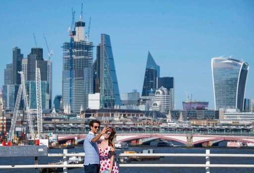 (Dominic Lipinski/PA via AP). Two people take a selfie as they stand on Waterloo Bridge, backdropped by the City of London financial district, as people enjoy the continuing spell of hot weather, Saturday June 30, 2018.