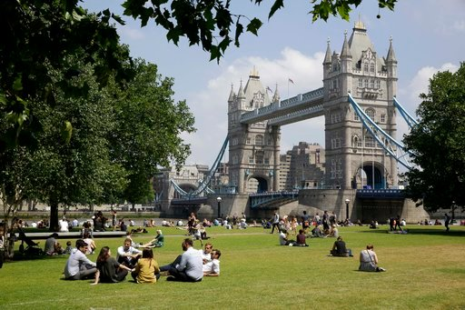 (AP Photo/Matt Dunham). People relax in the sun during lunchtime as they sit in Potters Fields Park, backdropped by the Tower Bridge, in London, Thursday, June 28, 2018.