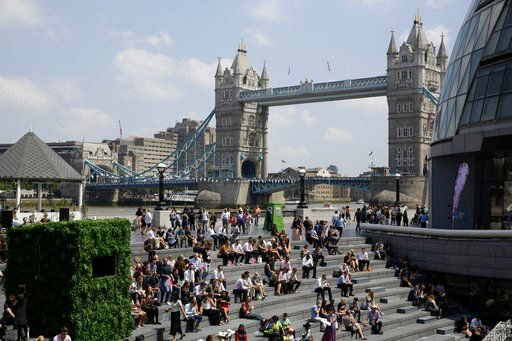 (AP Photo/Matt Dunham). On what has been the hottest week in Britain so far this year, people relax in the sun during lunchtime as they sit on the steps of The Scoop, a riverside amphitheatre, backdropped by the Tower of London, in London.