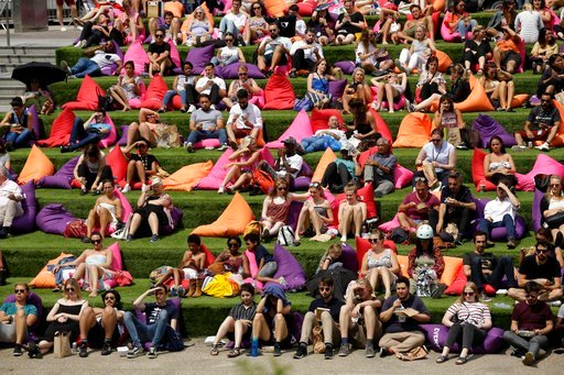 "(AP Photo/Matt Dunham). People watch ""The Never Ending Story"" movie on an outdoor cinema screen at Canalside Steps, Granary Square, London, Thursday, June 28, 2018, during hot weather."