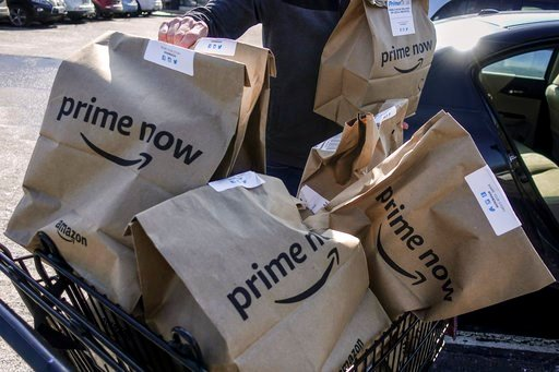 (AP Photo/John Minchillo, File). In this Feb. 8, 2018, file photo, Amazon Prime Now bags full of groceries are loaded for delivery by a part-time worker outside a Whole Foods store in Cincinnati.