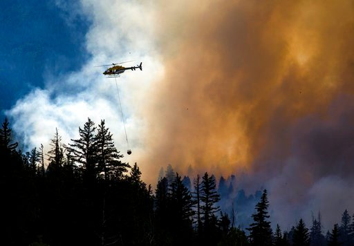(Hugh Carey/Summit Daily News via AP). A helicopter transports water to contain the Weston Pass Fire, Monday, July 2, 2018, near Fairplay, Colo. In Colorado, more than 2,500 homes were under evacuation orders as firefighters battled more than a half-do...