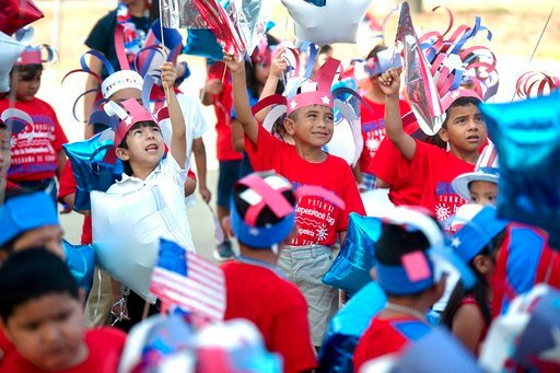 (Tim Monzingo/The Daily Sentinel via AP). Brooks-Quinn Jones Elementary School students wave flags over their heads as they prepare to march in the school's annual Independence Day Parade on Tuesday, July 3, 2018, in Nacogdoches, Texas. Students decora...