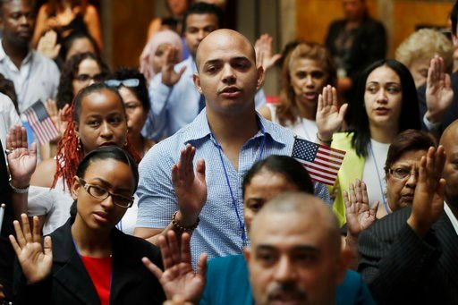 (AP Photo/Mark Lennihan). New citizens participate in a naturalization ceremony, Tuesday, July 3, 2018, at the New York Public Library. Two hundred people from 50 countries gained citizenship.