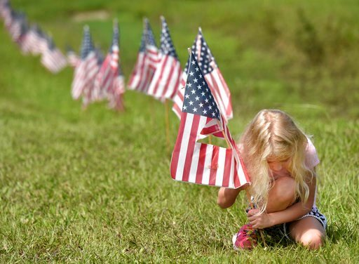 (Will Dickey/The Florida Times-Union via AP). Luna Chiarello, 6, helps her mother Silver put American flags out along the road in front of their family business, Robinson's Auto Parts, Tuesday, July 3, 2018 in Orange Mills, Fla., the day before Indepen...