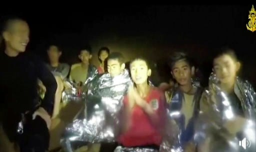(Thai Navy Seal via AP). In this July 3, 2018, image taken from video provided by the Thai Navy Seal, Thai boys are with Navy SEALs inside the cave, Mae Sai, northern Thailand.
