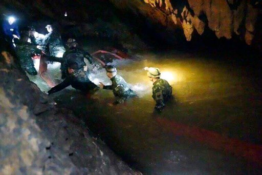 (Tham Luang Rescue Operation Center via AP, File). FILE - In this handout photo released by Tham Luang Rescue Operation Center, Thai rescue teams use headlamps to enter a pitch-black cave complex where 12 boys and their soccer coach went missing, in Ma...