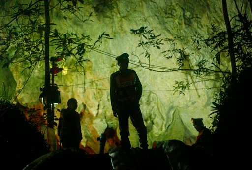 (AP Photo/Sakchai Lalit). FILE - In this Monday, July 2, 2018, file photo, Thai police stand in front of the entrance to a cave complex where 12 boys and their soccer coach went missing in Mae Sai, Chiang Rai province, in northern Thailand. The group w...