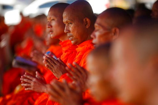 (AP Photo/Sakchai Lalit, File). FILE - In this Sunday, July 1, 2018, file photo, Thai Buddhist monks pray for the 12 boys and their soccer coach who went missing in a flooded cave in Mae Sai, Chiang Rai province, northern Thailand. The group was discov...