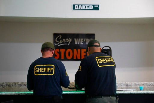 (AP Photo/Jae C. Hong). In this March 15, 2018 photo, two undercover Los Angeles County sheriff's deputies gather evidences during a raid at an illegal marijuana dispensary during a raid in Compton, Calif.