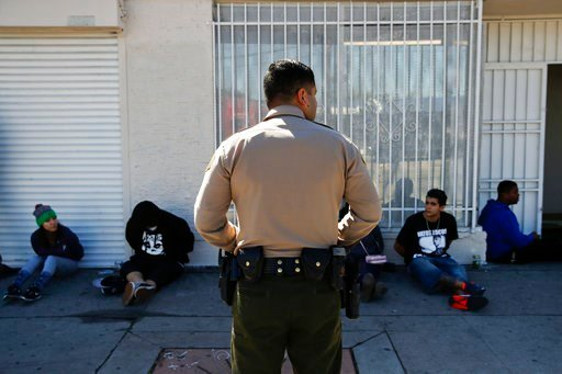 (AP Photo/Jae C. Hong). In this March 15, 2018 photo, a Los Angeles County Sheriff's deputy keeps watch on a group of people apprehended at an illegal marijuana dispensary in Compton, Calif. The number of outlaw dispensaries in the county greatly outnu...