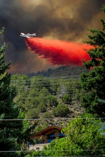 (Anna Stonehouse/The Aspen Times via AP). A plane drops fire retardant on homes in the area of Basalt, Colo., Wednesday, July 4, 2018, during the Lake Christine Fire.