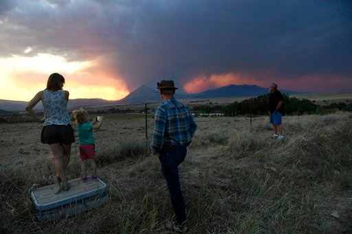 (Helen H. Richardson/The Denver Post via AP). Libby Barbee, left, her daughter Emmy and husband, Brandon Laird, and father, Ron Barbee, right, hold watch as the sun sets over the Spring Fire late Wednesday, July 4, 2018, in La Veta, Colo. They are evac...