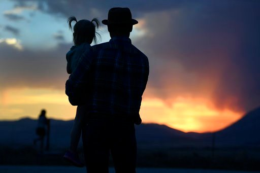 (Helen H. Richardson/The Denver Post via AP). Brandon Laird holds his daughter Emmy, 4, as they watch the sun set over the Spring Fire late Wednesday, July 4, 2018, in La Veta, Colo. They are evacuees who have a family cabin in Cuchara and hoping to go...