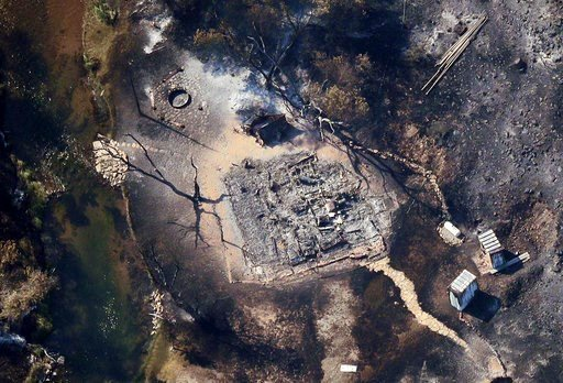(Scott G Winterton/The Deseret News via AP). In this aerial photo, a burnt out structure is visible through the smoke as a wildfire continues to burn east of Strawberry Reservoir, in Wasatch County, Utah, Tuesday, July 3, 2018. The Utah fire comes as h...