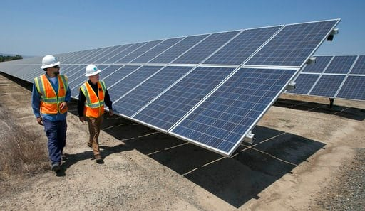 (AP Photo/Rich Pedroncelli, file). FILE - In this Aug. 17, 2017, file photo, Solar Tech Joshua Valdez, left, and Senior Plant Manager Tim Wisdom walk past solar panels at a Pacific Gas and Electric Solar Plant, in Dixon, Calif. A California legislative...