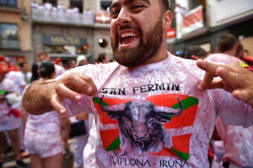 (AP Photo/Alvaro Barrientos). A revellers shows his wine stained t.shirt while waiting for the launch of the 'Chupinazo' rocket, to celebrate the official opening of the 2018 San Fermin fiestas with daily bull runs, bullfights, music and dancing in Pam...