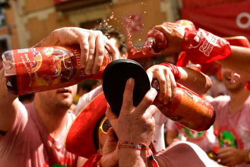 (AP Photo/Alvaro Barrientos). Revellers start celebrating early while waiting for the launch of the 'Chupinazo' rocket, to celebrate the official opening of the 2018 San Fermin fiestas with daily bull runs, bullfights, music and dancing in Pamplona, Sp...