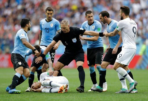 (AP Photo/Natacha Pisarenko). Uruguay players protest to referee Nestor Pitana of Argentina that France's Kylian Mbappe, on the ground, is overreacting after taking a dive during the quarterfinal match between Uruguay and France at the 2018 soccer Worl...