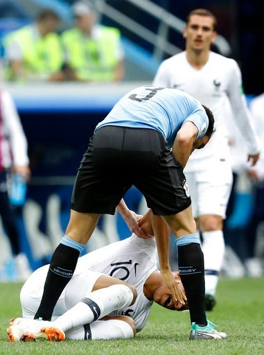 (AP Photo/David Vincent). Uruguay's Diego Godin bends down to France's Kylian Mbappe during the quarterfinal match between Uruguay and France at the 2018 soccer World Cup in the Nizhny Novgorod Stadium, in Nizhny Novgorod, Russia, Friday, July 6, 2018.