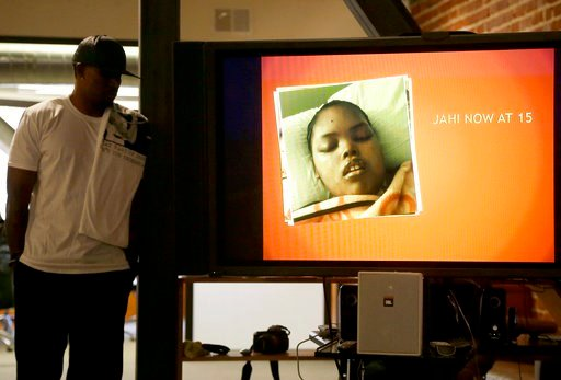 (AP Photo/Jeff Chiu, File). FILE - In this Dec. 23, 2015, file photo, a photo of Jahi McMath is shown on a video screen next to her uncle Timothy Whisenton at a news conference in San Francisco. The mother of a girl at the center of a medical and relig...