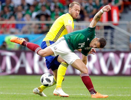 (AP Photo/Gregorio Borgia). FILE - In this Wednesday, June 27, 2018 file photo Sweden's Andreas Granqvist, rear, and Mexico's Javier Hernandez, front, challenge for the ball during the group F match between Mexico and Sweden, at the 2018 soccer World C...