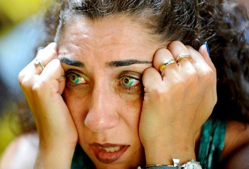 (Ken McGagh/The Metro West Daily News via AP). Wearing Brazilian flag contact lenses, Brazilian soccer fan Elizangela Santos, of Clinton, Mass., reacts after watching television coverage of Brazil's loss to Belgium in a World Cup soccer quarterfinal, F...