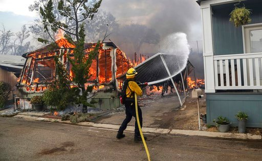 (Eduardo Contreras/The San Diego Union-Tribune via AP). Firefighters battle flames at the Alpine Oaks Estates mobile home park during a wildfire Friday, July 6, 2018, in Alpine, Calif. Dozens of fires are burning across the dry American West, fueled by...