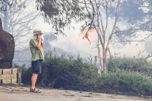 (Eduardo Contreras/The San Diego Union-Tribune via AP). Fred Begley makes a phone call as his home burns in the background during a wildfire Friday, July 6, 2018, in Alpine, Calif. Gusty winds fanned the flames as Southern California struggles through ...